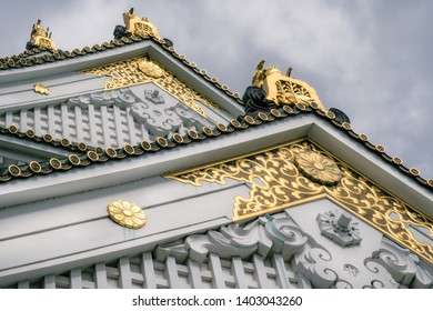 Plant inspired golden ornaments at Osaka Castle Pagoda with white walls and specific green roof tiles. Osaka Castle is one of the most famous historic landmarks in Japan.