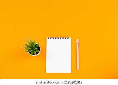 Plant, notepad and a pen. Study, take notes of writins a list. Copy space for your text.