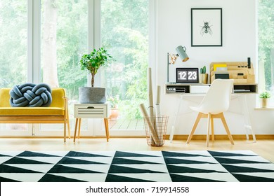 Plant on cabinet next to yellow sofa with blue pillow in spacious workspace with white chair at desk