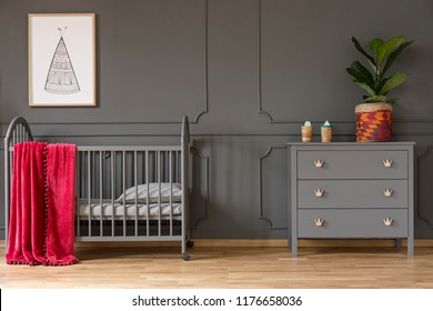 Plant on grey cabinet next to kid's bed with red blanket in bedroom interior with poster. Real photo