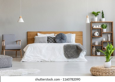 Plant on pouf in bright bedroom interior with wooden bed next to patterned armchair. Real photo