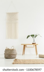 Plant on wooden table next to a basket in white boho interior with beige carpet