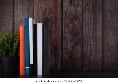 Plant pot and books in a line against a wooden panel background with blank areas for text.