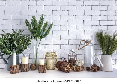 Plant pot, branch, flowers, candlelight and glass of bottle decorations on white table and brick wall background.