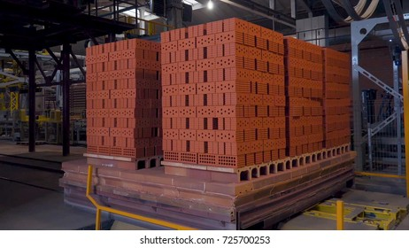 Plant for the production of bricks. Plant for production building material with ready brick, construction industrial. Production of bricks on plant. Workflow, close-up. Brick stacks. Many bricks