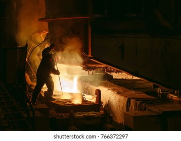 Plant for the production of steel. An electric melting furnace. Factory worker takes a sample for metal.