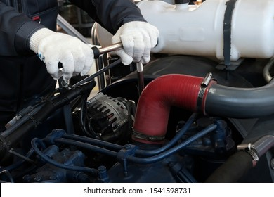Plant for the production of transport. The technician tightens the bolt with a socket wrench. Closeup of male hands tightening a nut on a tractor engine. Automotive industry. Heavy industry.