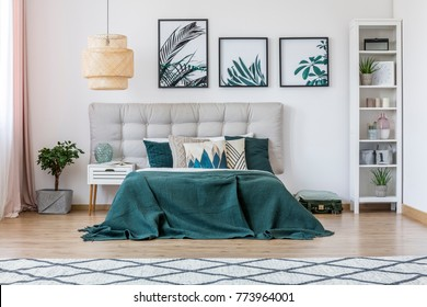 Plant, white cupboard and rattan lamp in green bedroom interior with bed with beige bedhead and leaves posters on the wall