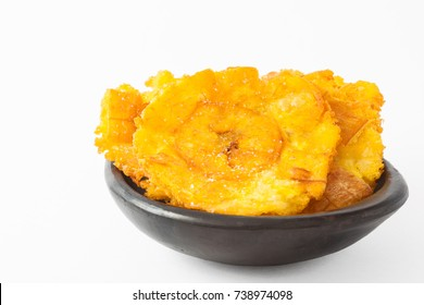 Plantain patacones on black ceramic dish isolated in white background
