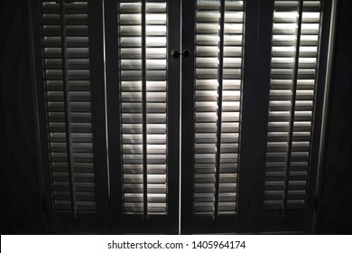 Plantation shutters are backlight by the sun and create a graphic background.