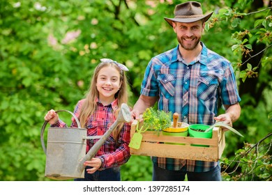 Planting season. Family garden. Maintain garden. Planting flowers. Family dad and daughter planting plants. Transplanting vegetables from nursery or gardening center. Plant your favorite veggies.