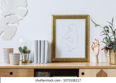 Plants, books and decorations with golden elements for a trendy and modern white living room interior standing on wooden furniture