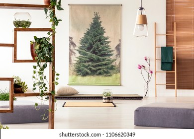 Plants on a wooden shelf in an oriental living room interior with a tatami, mat, poufs, ladder and tree poster