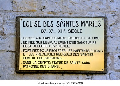 plaque explaining the history of the church of Saintes-Maries-de-la-Mer. Dedicated to Saints Mary Jacobe and Salome and the Crypt containing the statue of Saint Sara patron saint of the Gypsies.