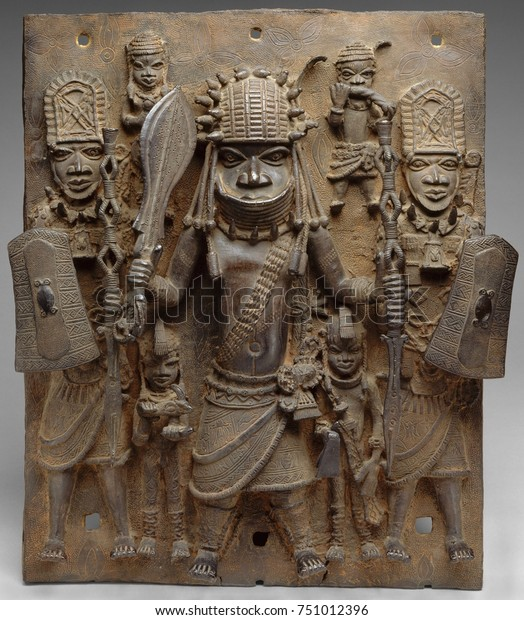 PLAQUE WARRIOR AND ATTENDANTS, 16th-17th c., Nigeria, Africa, Court of Benin, sculpture, cast brass. This work hung on the exterior of the royal palace in Benin City. In center is a warrior chief, fla