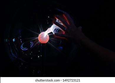 Plasma globe with hand touching it for electricity effect. Plasma ball. Plasma Lamp