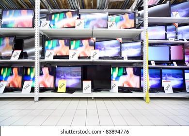Plasma TVs with big diagonal stand on shelves in large shop; wide range