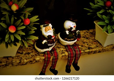 Plaster Santa Claus with welcome plate and ice cube sitting on sill