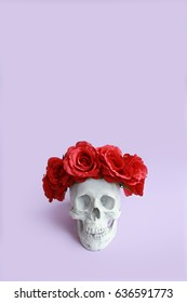 Plaster skull with red roses crown
