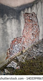 Plaster smashed from an old brick wall from an impact.