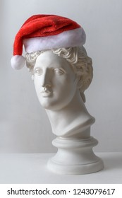 Plaster statue of the head of Smiling Apollo in a Christmas hat on the white background. Statue. Сreative. Gypsum statue of Apollo's head.  Christmas and New Year celebration. Christmas hats.