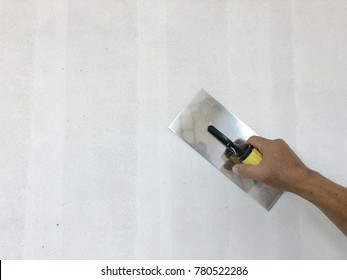 Plaster trowel. A hand holding a plaster trowel against the unfinished painted wall. Building and construction equipment with copy space.