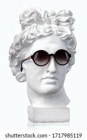 Plaster white bust Appolon head in sunglasses
