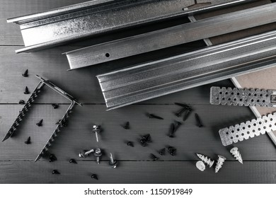 plasterboard profiles and fasteners on gray background. top view