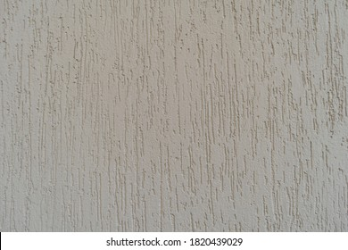 Plastered surface of a wall with light gray grooves. in Brazil known as grafiato.