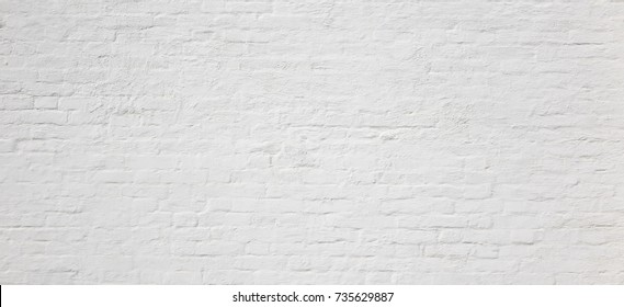 Plastered White Brick Wall. Light Empty Brickwall With Uneven Surface. Traces Of Aging Material, Chips, Cracks, Scrapes. Old Plaster, Whitewash Texture.