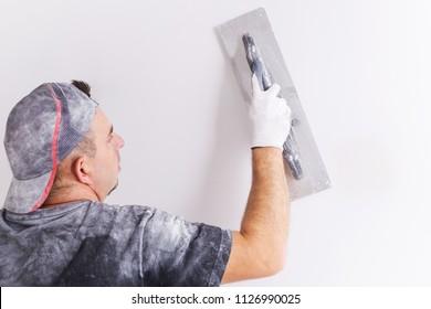 Plasterer applying gypsum plaster on the wall. House renovation concept.