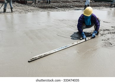 plasterer concrete cement work. using a trowel to smooth or leveling concrete slab floor work step of the building construction.