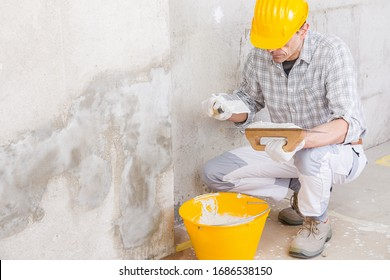 Plasterer covering a stained damp patch in a white wall with new plaster or masonry during renovations or maintenance on a house interior