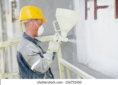 Plasterer facade builder worker with level at thermal insulation works
