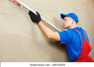 Plasterer at indoor wall renovation decoration with sleeker