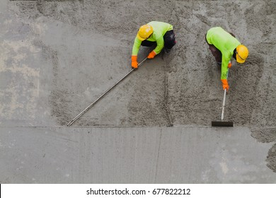 Plasterer laying concrete cement with trowel.