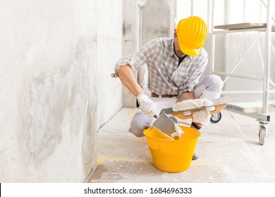 Plasterer loading new plaster from a bucket using a trowel to repair a wall of a house with damp stains from moisture or a leak