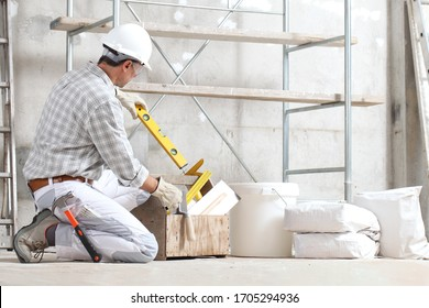 plasterer man construction worker takes the spirit level from the toolbox wear gloves, hard hat and protection glasses at interior building site with scaffolding. bucket and sacks