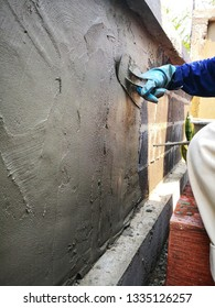 The plasterer is plastering to build the wall.