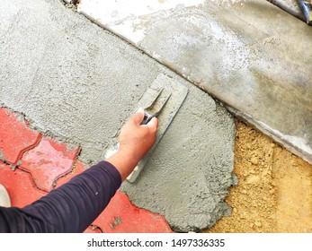 The plasterer was plastering the floor for footpath repairing.