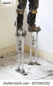 Plasterer plastering on stilts