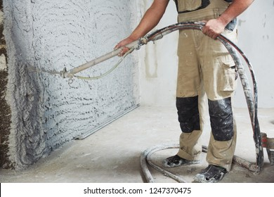 plastering the interior wall with an automatic spraying plaster pump machine