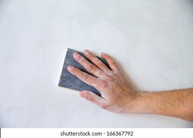 plastering man hand sanding the plaster in white wall