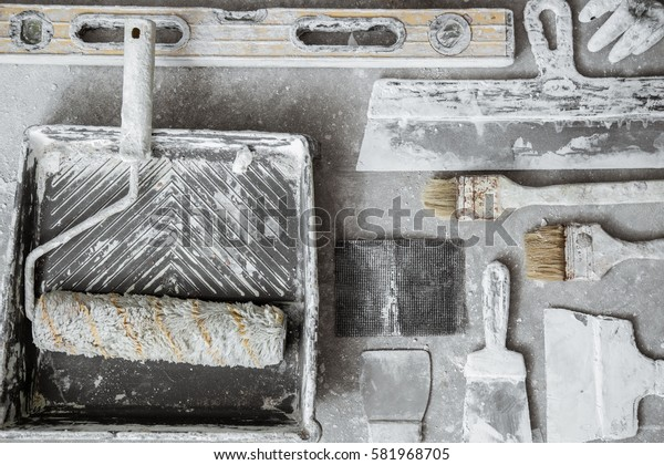 Plastering tools on cement background. View from top.