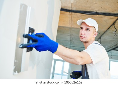 Plastering. Worker spackling a wall with putty