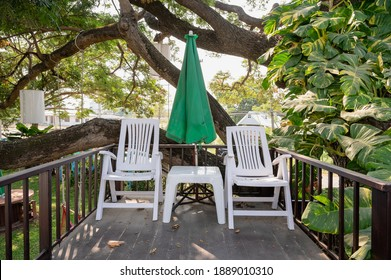 Plastic armchair with table and parasol on patio in the garden