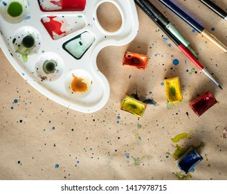 Plastic art palette with used brushes and opened paint boxes on paper-covered workshop table