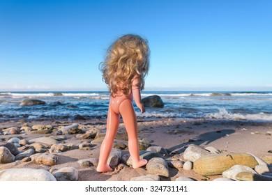 Plastic baby doll on the seashore