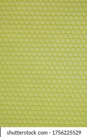 Plastic background in the form of salad-colored honeycombs. Textured corrugated background of salad color. Monotonous corrugated texture for an abstract background or for wallpaper of salad color.