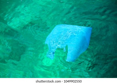 Plastic bag floating in clear water - sea pollution